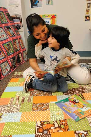 Gael Moran and his mother, Florentina Muñoz, enjoy quiet reading time on a homemade quilt. It is one of 55 quilts collected by nursing student Melissa House '11 and given to local Baltimore children.