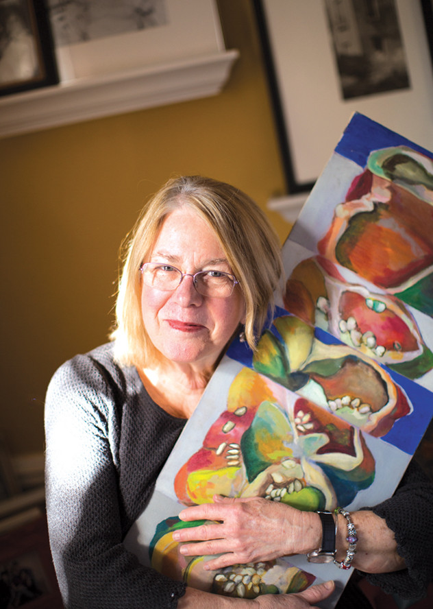 Pat Sullivan posing with one of her paintings of bell peppers